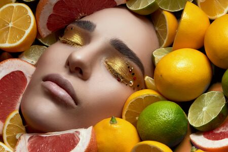 high Fashion model sleeping attractive girl with golden make-up lies on bright tasty fruits, lemon and lime citrus. High end retouch. Close up portrait