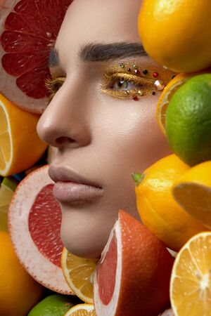 a tall girl model with golden, brilliant make-up lies on a background of bright fruits looking into the distance