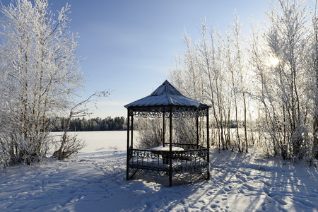 summerhouse: summerhouse on the shore of a frozen lake in winter Stock Photo