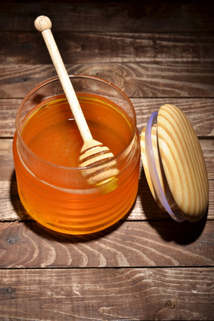 jar with honey and stick for honey photo
