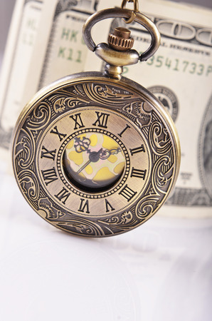 pocket watch and dollars on background