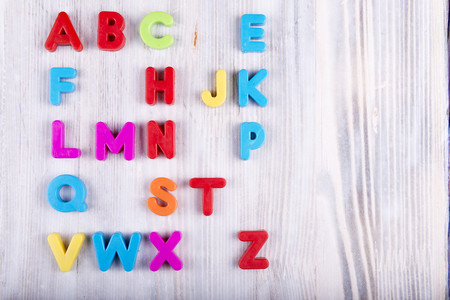 colorful plastic English alphabet on a white wooden background