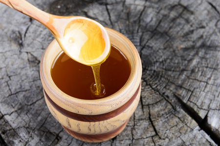 jar of honey and spoon with honey on a wooden background