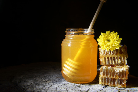 jar of honey and honeycombs on a wooden background