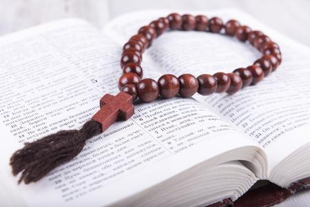 religion catolica: religiosa tema de libro sagrado y la cruz sobre un fondo de madera blanca