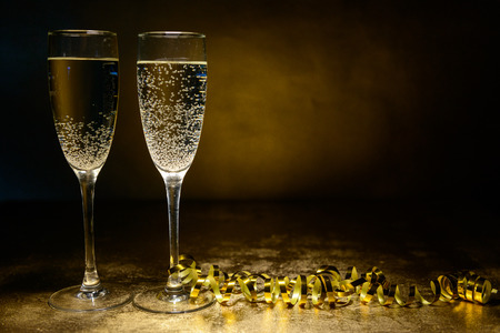 alcohol drinks: two glasses of champagne on a gold background. Christmas and New Year theme Stock Photo