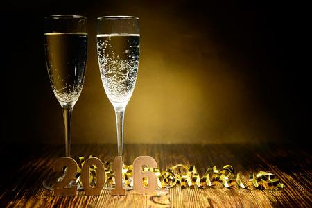 New Year: Dwa kieliszki szampana i złote figury 2016 na drewnianym tle Zdjęcie Seryjne