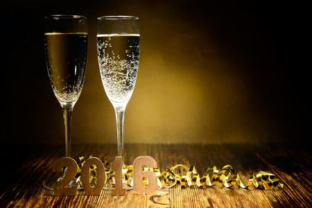 new year: Two glasses of champagne and gold figures 2016 on a wooden background Stock Photo