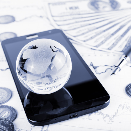 glass globe: business concept of glass globe, smart phone, coins, pen and money on trading chart Stock Photo