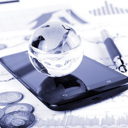 business globe: business concept of glass globe, smart phone, coins, pen and money on trading chart Stock Photo