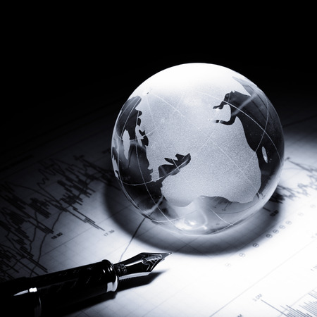 glass globe: business concept of a glass globe on a trading chart with pen