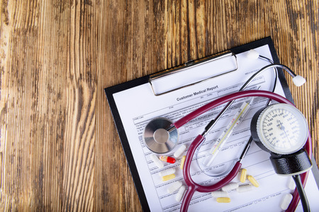 cold cure: Medical concept of medical report with stethoscope and medicines on wooden background