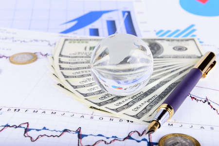 glass globe: business concept of a glass globe on charts and money