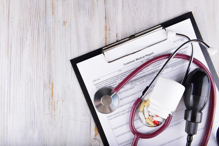 medical report: medical concept of medical report with pills and a stethoscope Stock Photo