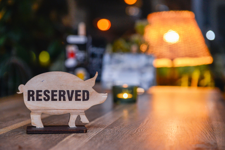 Reserved sign on a restaurant table. Sign in the form of pigs Standard-Bild