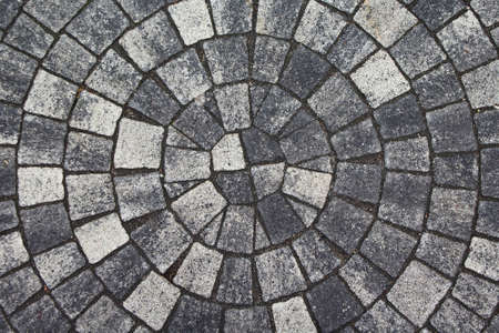 Background paving gray stones lined concentric circle. Visual pattern of the floor tiles background.