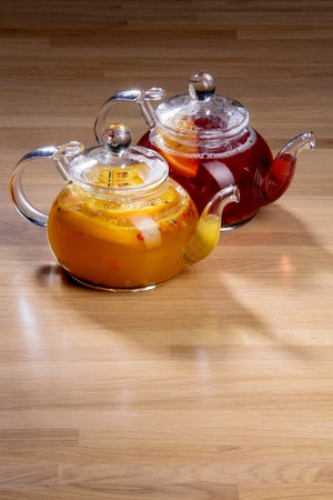 two glass teapots with sea buckthorn and raspberry tea on the table