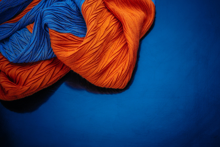 fragment of a blue-orange scarf texture on a blue background 免版税图像