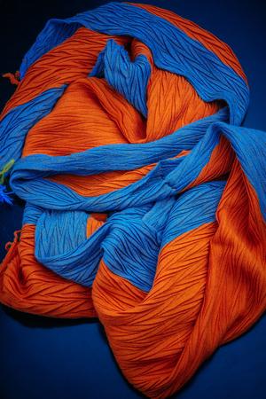 fragment of a blue-orange scarf texture on a blue background Foto de archivo