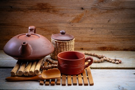 clay Chinese teapot on a wooden stand on an old board