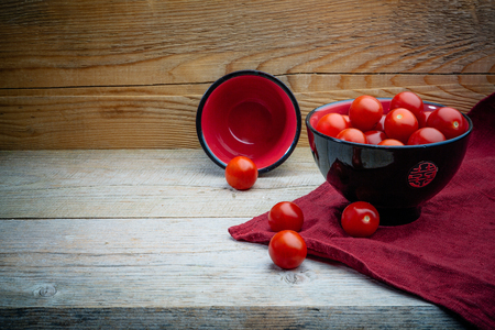 cherry tomatoes in a black and red pial on a wooden table with a red linen napkin Banque d'images