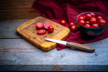 cherry tomatoes in a black and red pial on a wooden table with a red linen napkin and kitchen knife on a cutting board