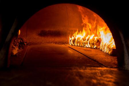 Close-up pizza in brandhoutoven met vlam erachter Stockfoto