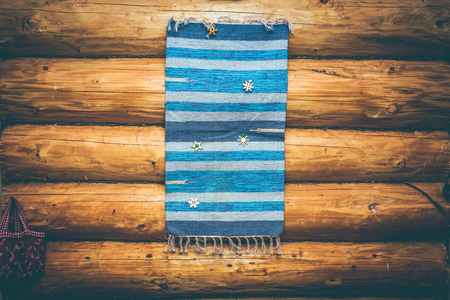 blue homespun rug on the log wall 版權商用圖片