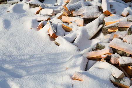 A pile of chopped wood under the snow.