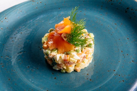 Russian salad on a blue plate with salmon and eggs