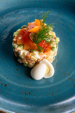 Russian salad on a green plate with salmon and eggs