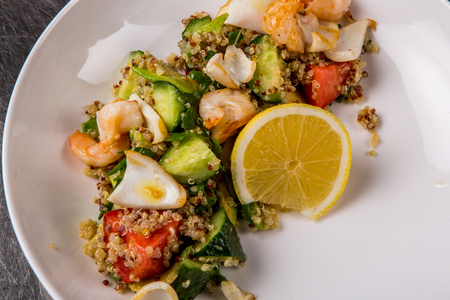 quinoa salad with tomato, cucumber, lemon and avocado on a white plate 版權商用圖片