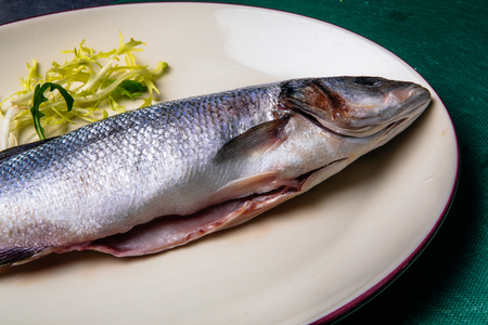 fresh raw gutted fish sea bass and sea bream on a white plate on a green table 版權商用圖片