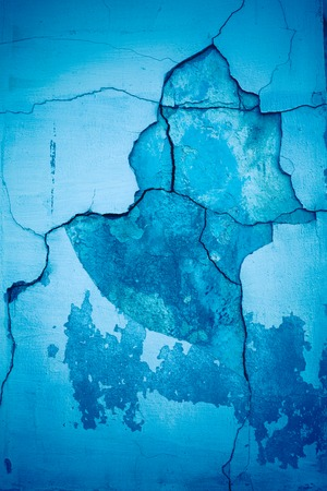 fragment of a blue wall with cracks on the plaster