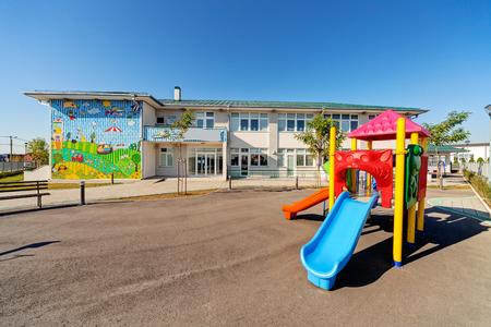화창한 날에 놀이터와 유치원 건물 외관 에디토리얼