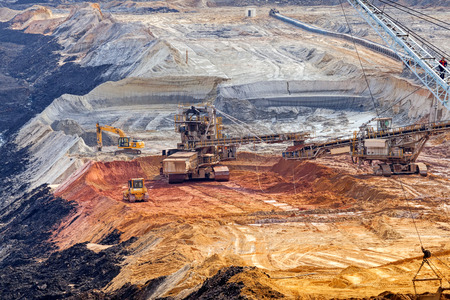 open mining pit with heavy machinery Editorial