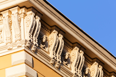 head stones: stone facade on classical building with ornaments and sculptures Stock Photo