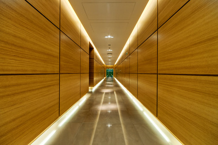 Corridor inside of modern building with wooden panels on walls