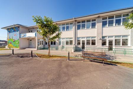 Edificio preescolar exterior con parque infantil en un día soleado Foto de archivo - 85084432