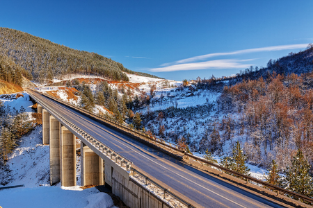 trip over: mountain bridge in winter with snow and blue sky, zlatibor mountain, serbia