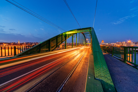 Steel bridge across river at night with artificial lightning Stock Photo