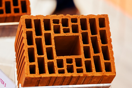 Detail of orange hollow clay block on a stand at construction fair Фото со стока