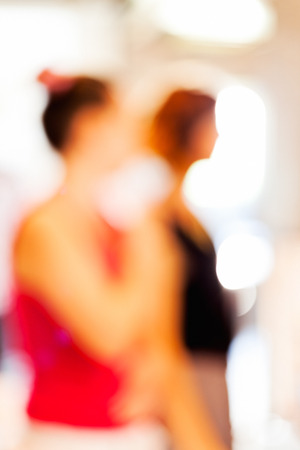 Two woman standing and looking at showpiece at tech expo; blurred 100%