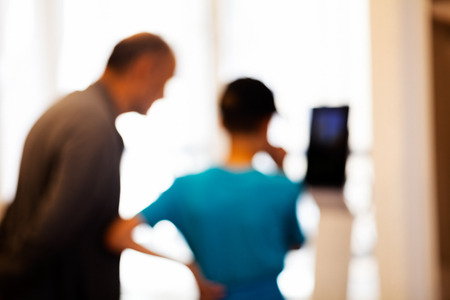 Old man and young boy looking at tablet showpiece at technology expo; blurred 100% Stock Photo