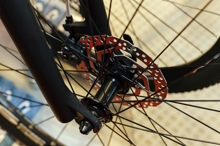 Closeup of bicycle front wheel and chrome shaft; note shallow depth of field