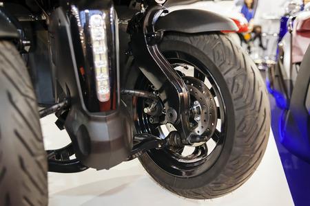 Foto van achterwiel met drie wielen en scooter; noteer ondiepe scherptediepte