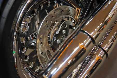 Closeup of quality steel motorcycle wheel with new tyre; note shallow depth of field