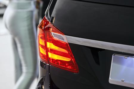 Close-up rode achterlicht op zwarte auto; noteer ondiepe scherptediepte