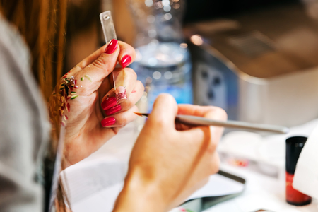 Young beautiful woman in a nail salon receiving a manicure by a professional beautician