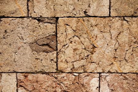 Een oude bruine de muurachtergrond van de kleurensteen.